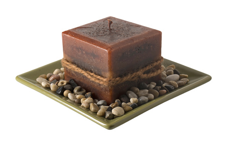 unlit: A decorative candle on a plate with stones, unlit.