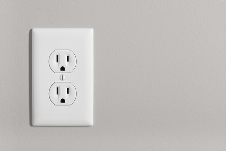 grounded plug: A white home electrical outlet on a light grey wall.