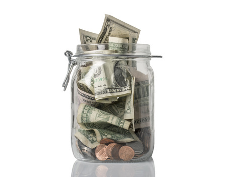 A tip jar or jar for savings filled over the top with American coins and bills. Stock Photo