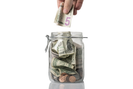 A tip or savings jar filled with American coins and bills and someone about to add a five dollar bill.