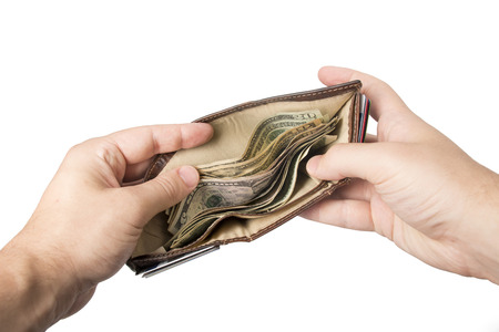 A wallet with cash (American dollars) being held open by a white male. Stock Photo