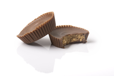 Two chocolate peanut butter cups, one with a bite taken out of it, on white with reflection and shadows. Stockfoto