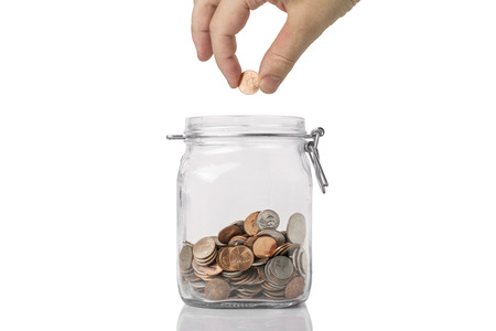 penny pinching: Penny Pinching or saving concept - a jar of American coins with a hand about to drop a penny into it.