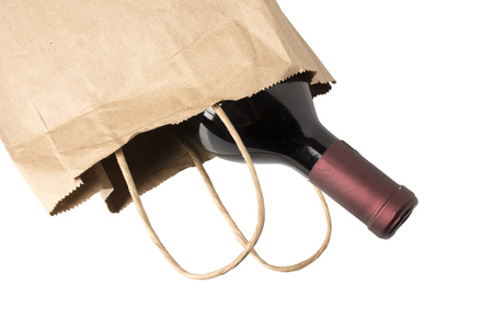 fancy bag: A bottle of red wine in a paper bag, overhead view, perhaps being given as a gift or bought at a liquor store, isolated on white.