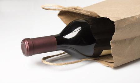 discreto: Una botella de vino tinto en una bolsa de papel, tal vez se da como un regalo o comprado en una tienda de licores, sobre un fondo blanco con la reflexión y la sombra
