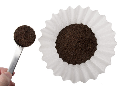 Ground coffee being scooped into a white basket style coffee filter, isolated on white.