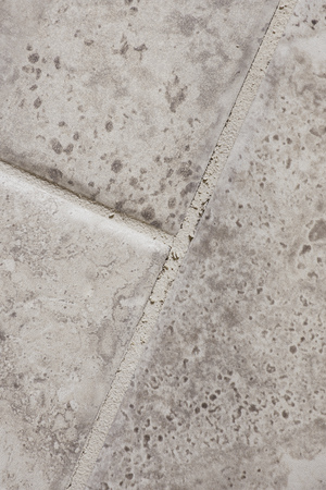 grout: Grout that has cracked in between tiles in a home bathroom.