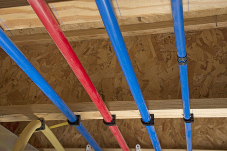 PEX pipes attached to the basement ceiling of a home, angled view. Stock Photo