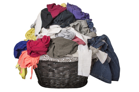 dirty: Dirty laundry piled up overflowing in a black basket, isolated on white. Stock Photo