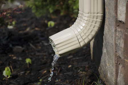 A rain gutter downspout with water coming out from the side, with a flower bed in the background. Shallow Depth of Field.