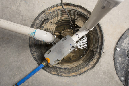 A sump pump installed in a basement of a home with a water powered backup system.