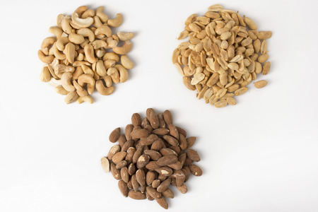 Three separate piles of nuts: cashews, almonds, and peanuts, on white Фото со стока