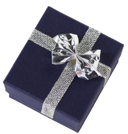 possibly: A tiny navy blue gift box with silver bow, possibly for jewelry, closed, isolated on white. Stock Photo