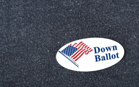 Closeup of a sticker with an American flag and the words Down Ballot placed on a navy shirt. Stock Photo