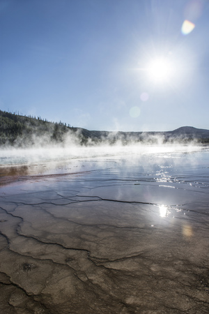 Ripples and Steam with reflections and sun flare in Midway Geyser Basin, near Grand Prismatic Spring, Yellowstone National Park, United States Stock Photo