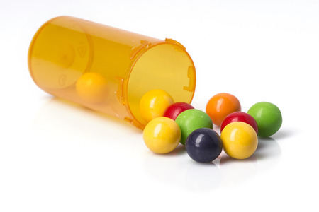 A prescription bottle with brightly colored candies spilling out of it. Stock Photo