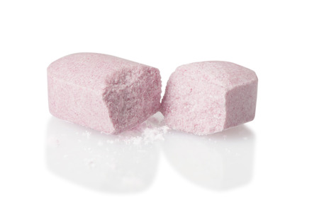 pharmaceutical company: A pink pill that has been cut in half - expensive medication concept