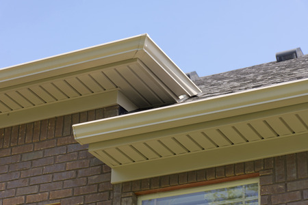 Roof showing gutters and soffit on the back of a brick house. Standard-Bild