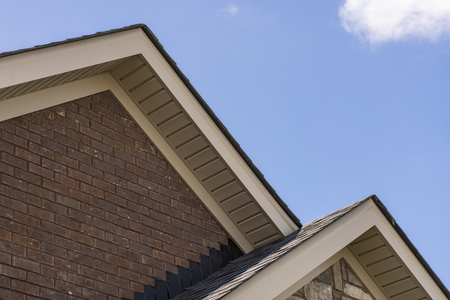 Roof showing soffit on the front of a brick and stone house. Stock Photo