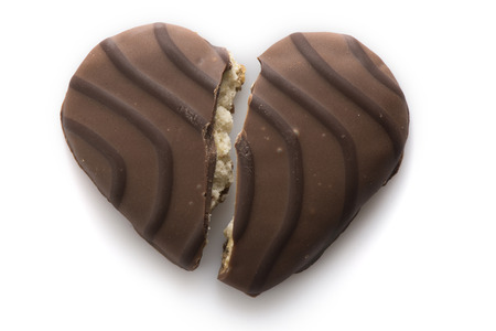 A heart-shaped chocolate-covered european wafer cookie broken down the middle. Stock Photo