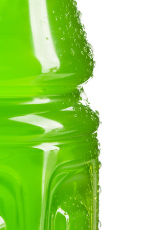 Side of a bottle of green colored sports or energy drink with water droplets with white background.