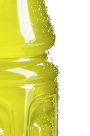 Side of a bottle of yellow colored sports or energy drink with water droplets with white background.