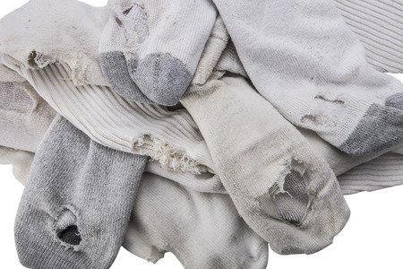 Pile of old white socks with holes overhead.