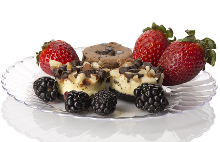 Dessert Plate with Mini Cheesecakes and Fruit, on a clear plate on white with reflection