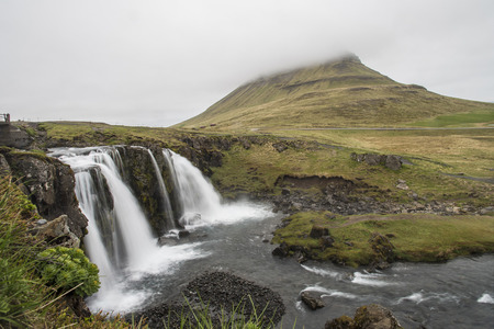 Long Exposure of Kirkjufellsfoss with Kirkjufell Mountain in the background, obscured by fog (Iceland) Фото со стока