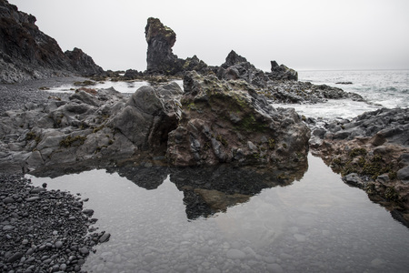 Rock formations on Djúpalónssandur beach, Iceland reflecting in the water.