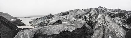 Panoramic image of Sólheimajökull Glacier in Iceland looking back to the path onto the glacier and towering over the viewer.