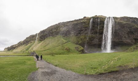 Tourists walk on a path near Seljalandsfoss on an overcast day. Editorial use only.