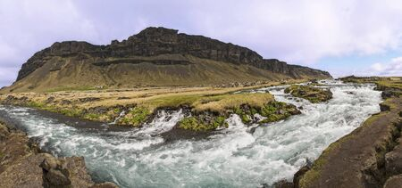 Panoramic view of rapids and small waterfalls on the Fossálar river in southern Iceland. Banco de Imagens