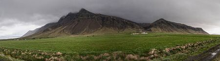 Landscape showing mountains, a field and Icelandic horses far in the distance. Фото со стока