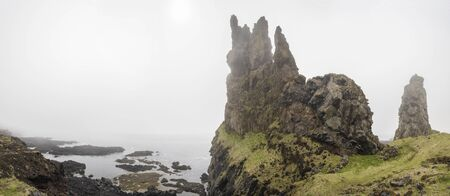 Panoramic view of Londrangar, Iceland on a Foggy day showing the cliffs and coastline.