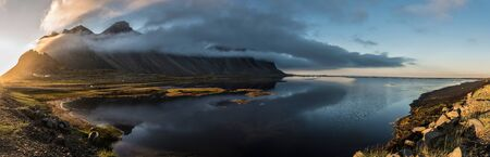 Panoramic view of a Sunset in Stokksnes, Iceland with Vestrahorn mountain obscured by clouds, and water in the foreground. Фото со стока