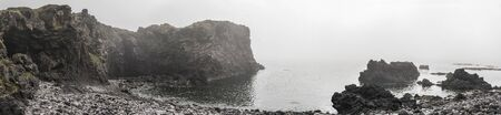Panoramic view of Badstofa Rock Foamation and ocean on a foggy day, Iceland