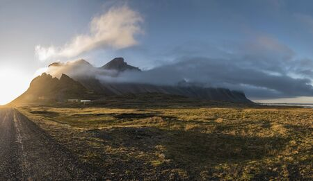 Panoramic Sunset in Stokksnes, Iceland with Vestrahorn mountain visible, partially obscured by clouds.