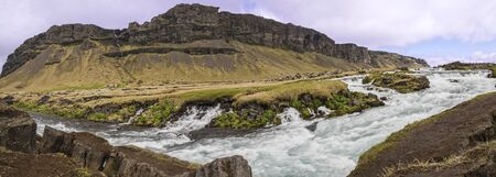 Panoramic long exposure of rapids and small waterfalls on the Fossálar river in southern Iceland.