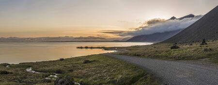 Panoramic view of a sunset behind mountains and fog and a winding Gravel Road near Stokksnes, Iceland Фото со стока