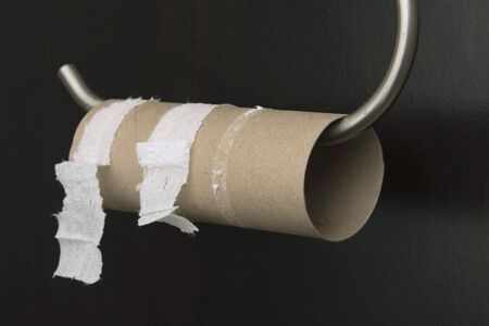 An Empty toilet paper roll on a holder against a black wall.