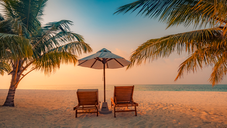 Beautiful beach. Chairs on the sandy beach near the sea. Summer vacation and holiday concept. Inspirational tropical beach. Tranquil scenery, relaxing beach, tropical landscape design. Moody landscape Banco de Imagens