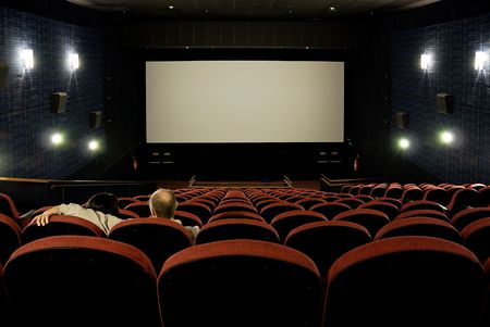 A couple sitting in an empty cinema, with red seats and blank screen.