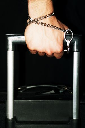 Hand chained to luggage representing deportationimmigration. Stock Photo