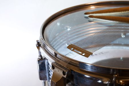 Detail of a snare drum (upside down) with drumsticks resting on it. Stock Photo