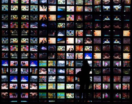 Small silhouette of a girl (from behind) with several TV screens in the back.