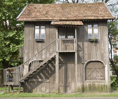two floors: Front shot of an old-style wooden house with two floors and wooden staircase Stock Photo