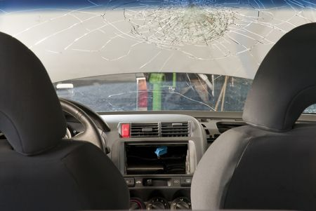 Detail shot of a shattered car windshield in a repair shop. Shot from inside the car.