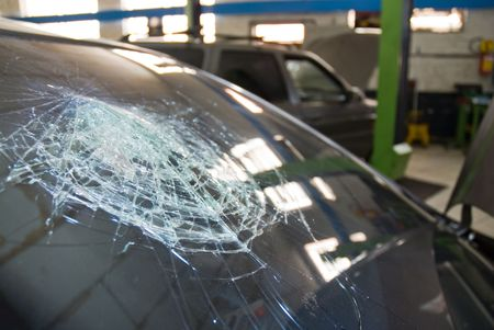 Detail shot of a shattered car windshield in a repair shop.