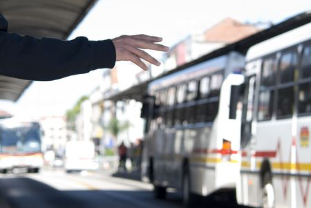 Cropped shot of unrecognisable passenger stopping a bus (in the background). Arm and hand detail.